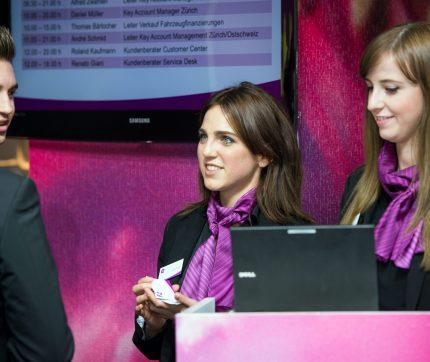 Zwei Empfangs-Mitarbeiterinnen stehen hinter dem Laptop beim Check-in eines Events.