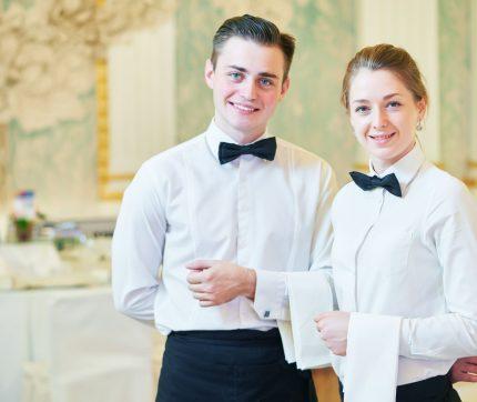 Ein junger Mann und eine junge Frau in Gastronomie-Arbeitskleidung lächeln in die Kamera und repräsentieren das Servicepersonal.