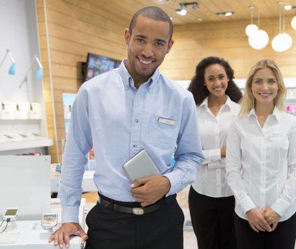 Drei Sales Mitarbeitende in einem Mobiltelefongeschäft