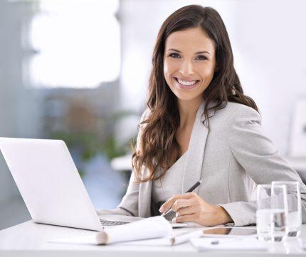 Eine Frau sitzt lächelnd an ihrem Arbeitsplatz hinter ihrem Laptop und ihren Notizen.