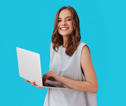 Eine junge Frau hält lächelnd einen Laptop