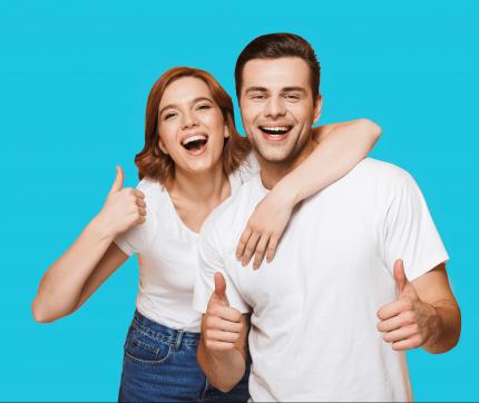 Eine Frau hat ihren Arm um die Schultern eines Mannes gelegt, während beide die Daumen hochhalten